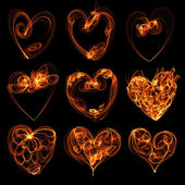 Flamy heart symbols on the black background — 图库照片
