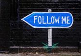 Follow me roadsign on black brick wall — 图库照片