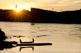 Silhouette of a young men carrying canoe away from lake in sunset — Stock Photo
