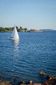 Sailboat and rocky coastline in nice clean sea — Stock Photo