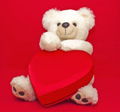 Teddy bear with gift box in heart shape — Stock Photo