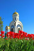 Red tulips in front of a Christian church — Foto de Stock