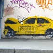 Graffiti on the wall, painted yellow taxi car, crashed into a te — Stock Photo #42257189