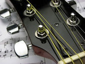 A guitar fretboard and music — Stockfoto