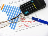 A pen, a graph, a calculator and glasse — Stock Photo