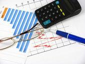 Een pen, een grafiek, een rekenmachine en glasplaten — Stockfoto
