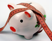 A measuring tape and a moneybox — Stock Photo