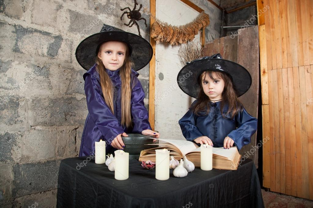 Two little witches conjure in an abandoned house  Stock Photo #12640453