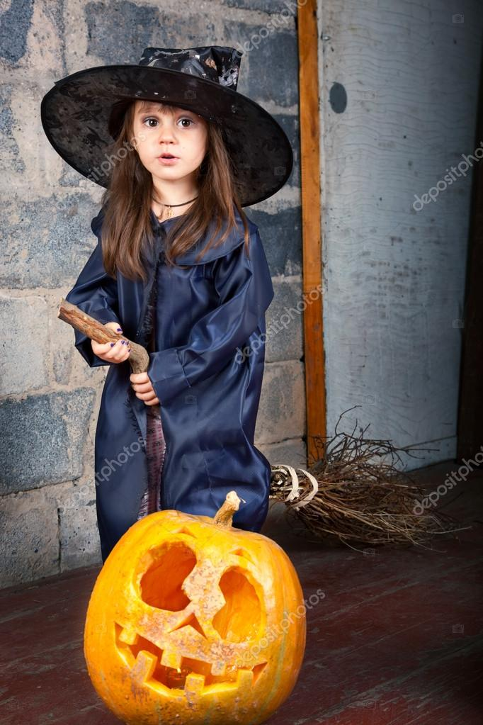 Little witch with a broom in an old abandoned house with Halloween pumpkins — Photo #12640576