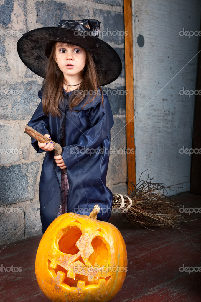 Little witch with a broom in an old abandoned house with Halloween pumpkins — Stockfoto #12640576
