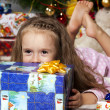 The girl with a gift under the Christmas tree — 图库照片