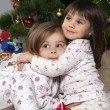 Two girls with a gift under the Christmas tree — 图库照片