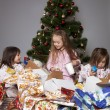 Three girls under the Christmas tree with gifts — Stock Photo #14232721