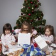 Three girls under the Christmas tree with gifts — Stock Photo #14232725