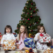Three girls under the Christmas tree with gifts — Stock Photo