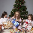 Three girls under the Christmas tree with gifts — Stock Photo #14232735