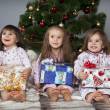 Stock Photo: Three girls under Christmas tree with gifts