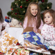 Three girls under the Christmas tree with gifts — Stock Photo #14232755