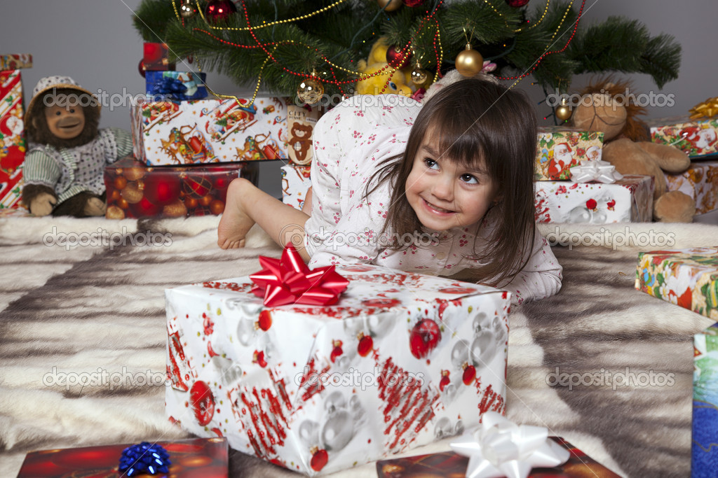 Girl in pajamas lying under the Christmas tree with gift in hand — Stock Photo #14232695