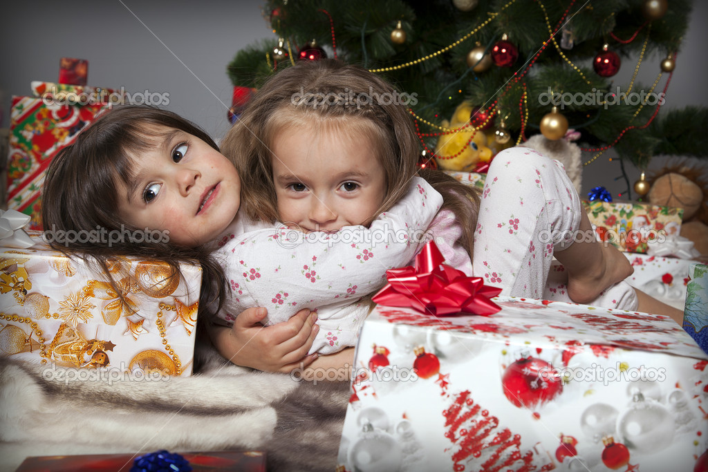 Two girls in pajamas sitting under the Christmas tree with gifts — Stock Photo #14232701