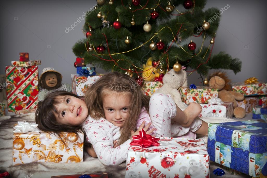 Two girls in pajamas sitting under the Christmas tree with gifts — Stock Photo #14232709