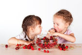 Two little girls with a full bowl of cherry — Stock Photo