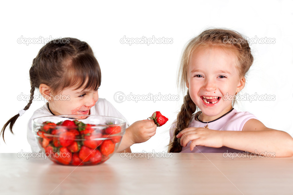 Two little girls feed each other strawberries with a full bowl of strawberries — Stock Photo #17353723