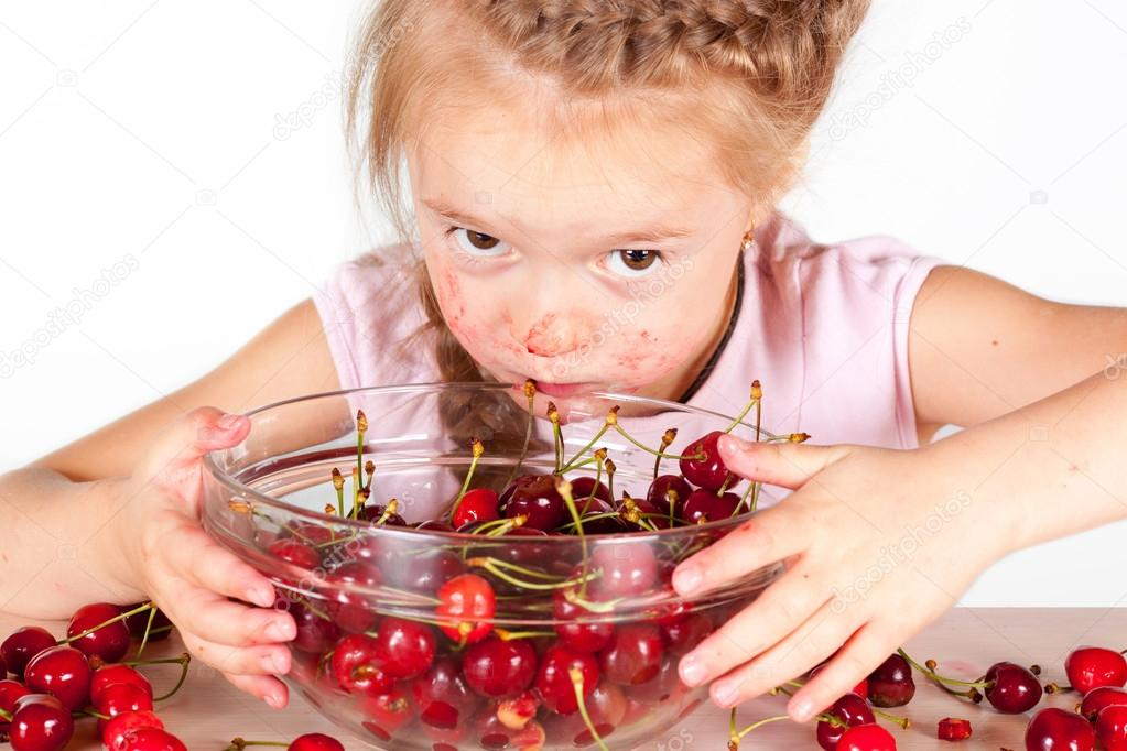 Little girl eating cherry with a full bowl of cherry  Stock Photo #17353799