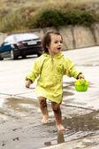 Fille saute dans une flaque d'eau — Photo