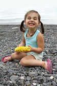 Adorable girl eating corn on the coast — Stock Photo