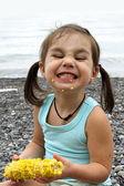 Adorable girl eating corn on the coast — Стоковое фото
