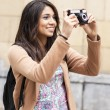 Young smiling woman taking pictures by city. — Stock Photo