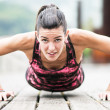 Young Woman Exercising Push-Ups on Wooden Floor. — Stock Photo
