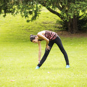Young sporty woman stretches in the park. — 图库照片