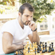 Pensive man plays chess in the park. — Stock Photo