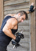 Man exercising dumbbells on wooden background. — Stock Photo