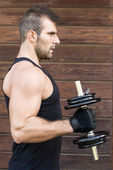 Portrait of sporty man exercising dumbbells. — 图库照片