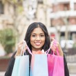 Smiling attractive woman holding shopping bags. — Stock Photo