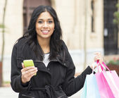 Attractive woman holding shopping bags and phone. — Foto de Stock