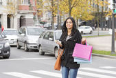 Beautiful smiling woman crossing street with shopping bags and p — Fotografia Stock