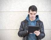 Man using tablet computer on gray background. — Stock Photo