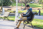 Man sitting and using tablet computer in the park. — Stock Photo