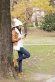 Smiling woman using tablet computer in the park. — Stock Photo