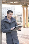 Man holding tablet computer in the park. — Stock Photo