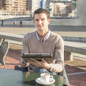 Businessman sitting on terrace bar with coffee cup and laptop ta — Stock Photo