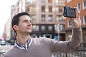 Portrait of man taking photo with retro camera in the street. — Stock Photo