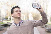 Man taking a picture of himself with smartphone, outdoor. — Stock Photo