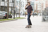 Skateboarder down the hill in the street and talking by phone. — Stock Photo
