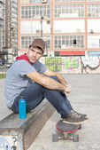 Skateboarder sitting in the park with skate and bottle of energy — ストック写真