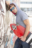 Portrait of pensive and serious skateboarder with skate, outdoor — Stok fotoğraf